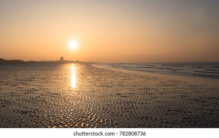 Golden beach by the sea at sunset in Belgium, Nieuwpoort. Beautiful reflection of the sun on water. Dreamy and romantic feeling