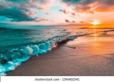 Golden beach sunset on a tropical island. Orange, teal, pink tones