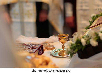 Golden beautiful shiny chalice with wine holy bible and rood on church altar on blur background