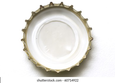 Golden beer cap macro over white background