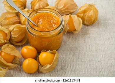 Golden berry jam in jar or cape gooseberries background with space