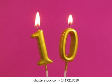 Golden birthday candle on pink background, number 10