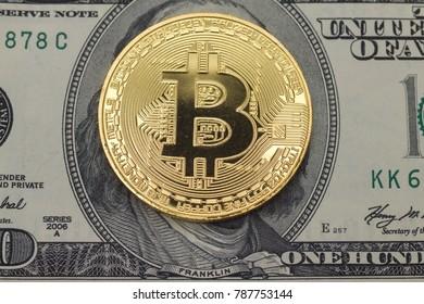 golden bit coin lay on face side  hundred  dollar  bill