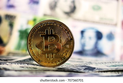Golden Bitcoin against of different banknotes on background. Cryptocurrency Trading concept .