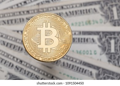 Golden Bitcoin (BTC) cryptocurrency coin and dollar bills in background