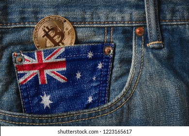 Golden BITCOIN (BTC) cryptocurrency in the pocket of jeans with the flag of Commonwealth of Australia on Jeans Denim Texture.