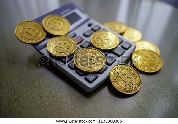 Golden bitcoin with calculator on wooden table as background. Fees and taxes on cryptocurrency investments