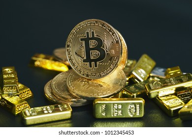 Golden bitcoin coin and Gold bars on the black leather.