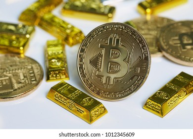 Golden bitcoin coin and Gold bars on the white background.