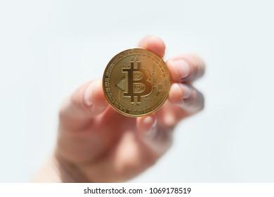 Golden bitcoin coin in man hand closeup. E-business cryptocurrency concept