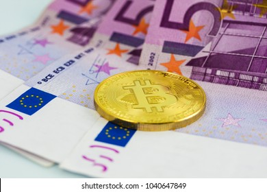 Golden bitcoin coin on a background with 500 euro bills, european paper currency. Crypto-currency concept.