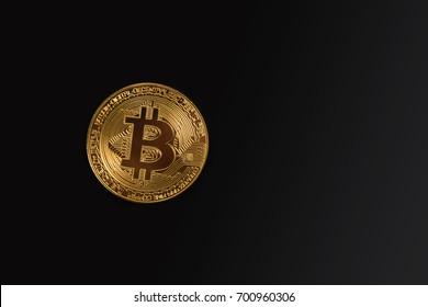 Golden Bitcoin coin on the black background