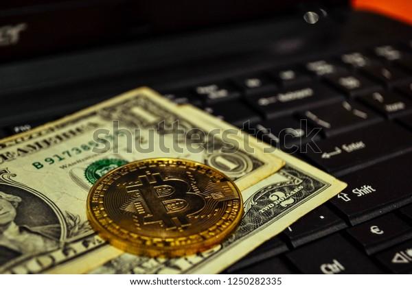 Golden bitcoin coin on a black keyboard