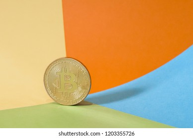 Golden Bitcoin coin on a brightly colored geometric background