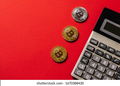 golden bitcoin coin on calculator close up isolated on red background