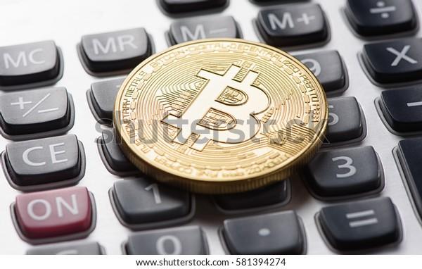 golden bitcoin coin on calculator close up