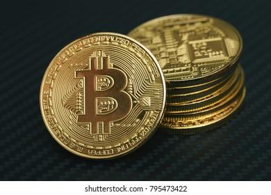 Golden bitcoin coin on the carbon Sheet.