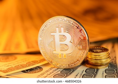 Golden Bitcoin coin on different currency bills. Electronic money exchange concept