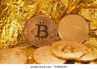 Golden bitcoin coin on gold background.