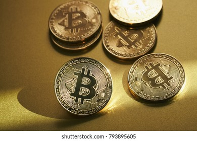 Golden bitcoin coin on gold plate.