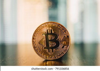 Golden bitcoin coin on a reflection surface with green and yellow striped background