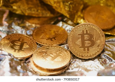 Golden bitcoin coin on silver background.