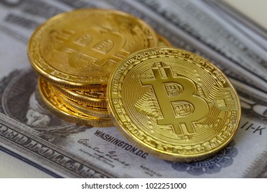 Golden Bitcoin coin on us dollars bills in background,  crypto-currency digital bit coin in hand, virtual money concept