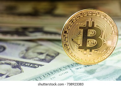 golden bitcoin coin on us dollars close up. Bitcoins. Physical bitcoins. Digital currency. The concept of cryptocurrency mining. Coin with bitcoin symbols