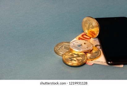 Golden Bitcoin coins with 10 Euro note and a black smart phone on a pale blue background.