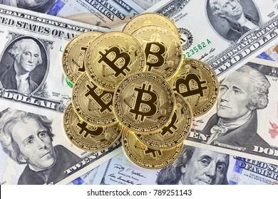 Golden bitcoin coins on dollar bills background.