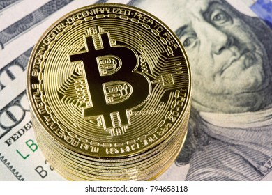 Golden bitcoin coins on one hundred dollar bills background.