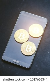Golden bitcoin coins on a smart phone. Virtual currency. Crypto currency. New virtual money. Lens flare