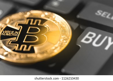 golden bitcoin and computer keyboard with buttons buy & sell