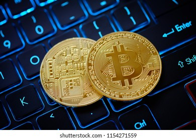 Golden Bitcoin as crypto currency on top of illuminated keyboard