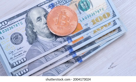 golden Bitcoin cryptocurrency coins on one hundred US Dollar. Virtual cryptocurrency concept. Bitcoin BTC cryptocurrency coins and banknotes of one US Dollar. BTC vs USD