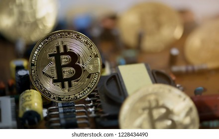 Golden Bitcoin Cryptocurrency on circuit board. Close-up shot.