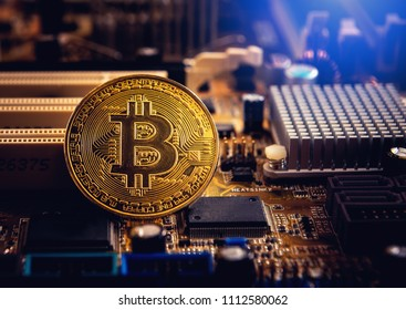 Golden bitcoin cryptocurrency on computer electronic circuit board.
