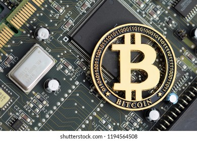 Golden bitcoin cryptocurrency on computer electronic circuit board. Cybercrime background