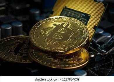 Golden Bitcoin Cryptocurrency on computer circuit board CPU. Macro shot.