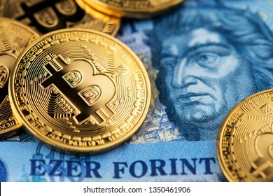 Golden Bitcoin Cryptocurrency on Hungarian Forint banknotes close up image. Cryptocurrency Bitcoin virtual money with Hungarian Forint money. Hungary Bitcoin Forint Cryptocurrency Blockchain BTC
