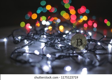 Golden Bitcoin currency. Festive atmosphere. Colorful Christmas tree lights in the background. BTC is a cryptocurrency and is the first decentralized peer-to-peer payment network.