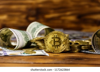 Golden bitcoin and dollars on wooden background