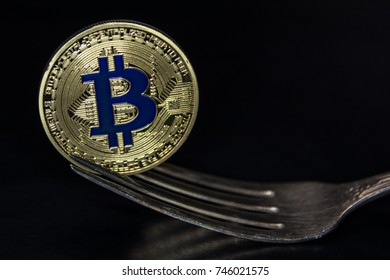 golden bitcoin fork on black background