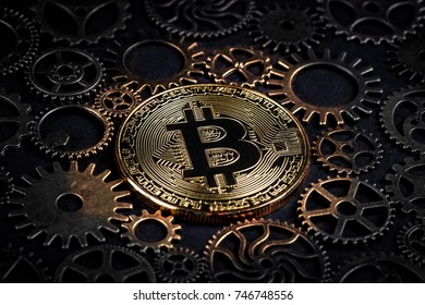 Golden bitcoin glowing in the middle of intricate cog wheels closeup. Crypto currency concept