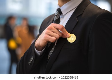 Golden bitcoin in hand of business man with black suit