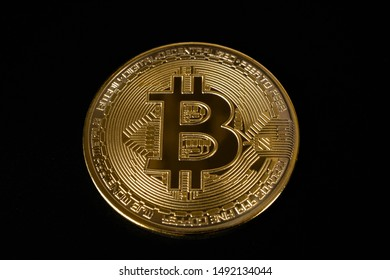 Golden bitcoin isolated on a deep black background