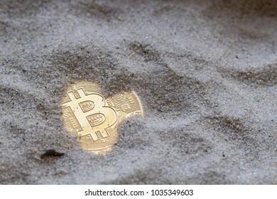 golden bitcoin lies in the sand