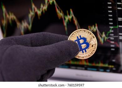 golden bitcoin in man's fingers weared in black gloves