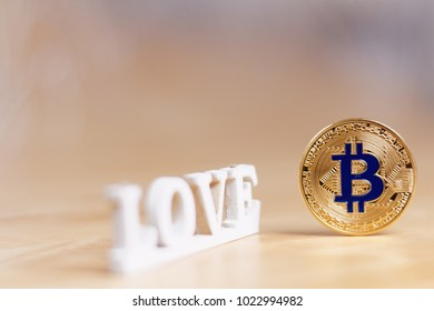 Golden bitcoin - most popular cryptocurrency and love inscription on light background