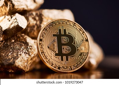 Golden bitcoin next to gold lumps representing futuristic world trends both isolated on black background. Digital virtual currency electronic money mining blockchain exchange innovation business